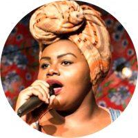 Mulher preta, educadora, ativista, MC e cantora. É integrante do coletivo Black Power e da produtora Tentacool. Traz em sua práxis diária na educação o Rap, como forma de combate a uma educação tradicional e colonizadora. Atualmente é professora da SME e atua lecionando em duas escolas no Grajaú, zona sul de São Paulo.