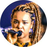 Inicia no Hip Hop como Mc em 2008 no grupo Odisseia das Flores. Durante sua trajetória, realizou diversas parcerias e participações musicais ao lado de grandes nomes do Rap. Artesã, cantora, compositora e arte-educadora, atua também em projetos sociais, culturais artísticos e educacionais. Fazendo parte e colaborando com coletivos que atuam nas periferias do Brasil.